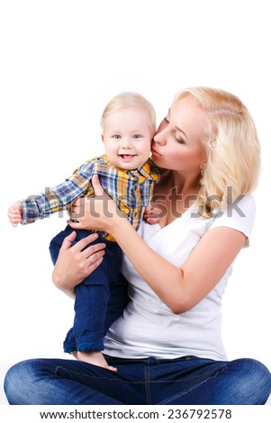 Happy cheerful family. Mother and baby kissing, laughing and hugging. Happy family mother kissing baby on white background. Studio shot - stock photo