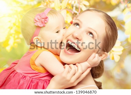 Happy cheerful family. Mother and baby kissing, laughing and hugging in nature outdoors - stock photo