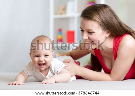 Happy cheerful family. Mother and baby playing, laughing and hugging - stock photo