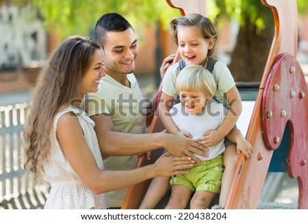 Happy cheerful family of four at children's playground. Focus on woman  - stock photo