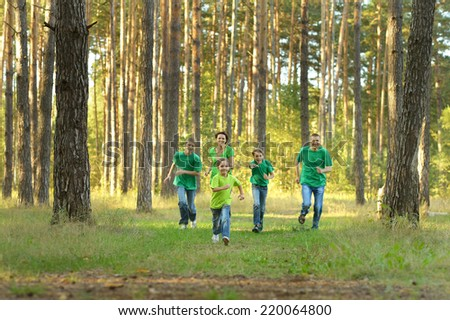 Happy cheerful family running in summer park - stock photo