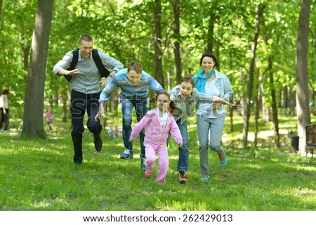 Happy cheerful family walking in summer park