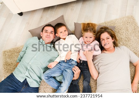 happy cheerful family with young kids playing together in  carpet at home  - stock photo