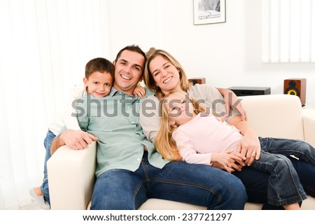 happy cheerful family with young kids playing together in the sofa at home