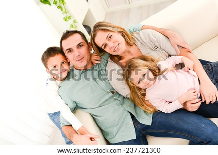 happy cheerful family with young kids playing together in the sofa at home  - stock photo