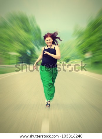 happy, cheerful girl running down the road - stock photo