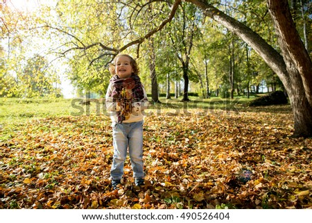 Happy cheerful kid playing in the autumn park. Little girl throwing fallen yellow leaves. Sunny weather, fresh air. Carefree childhood concept. Healthy lifestyle.