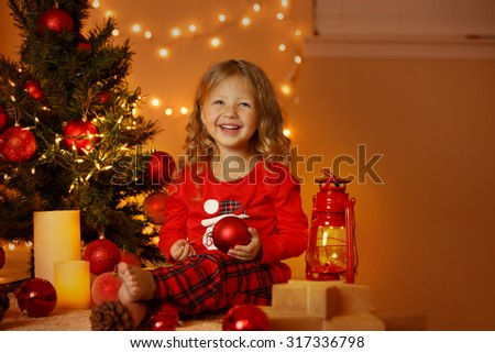 Happy cheerful little girl excited at Christmas Eve, sitting under decorated illuminated Christmas Tree. Greeting card or cover, horizontal with copy space.  - stock photo
