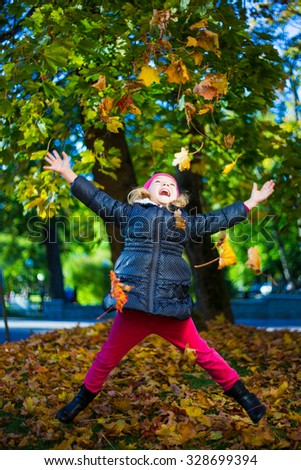 happy cheerful little girl playing with maple leaves in park