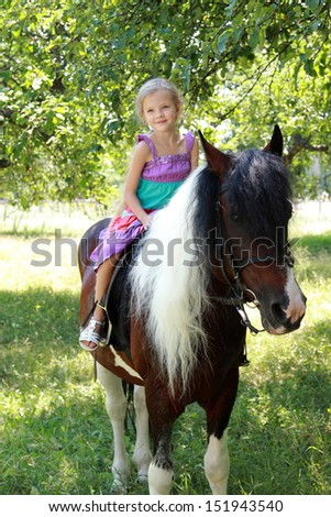 Happy cheerful little girl with long healthy hair is sitting on a horse and smiling - stock photo