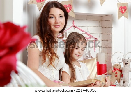 Happy cheerful mother and daughter in white dresses in a romantic atmosphere on Valentine's Day - stock photo