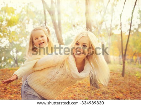 Happy cheerful mother holding smiling baby girl and play  together in sunny autumn park, both dressed in white knitted sweaters, autumn fashion. - stock photo