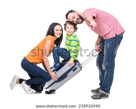 Happy cheerful parents and their son on a suitcase, isolated on white background. - stock photo