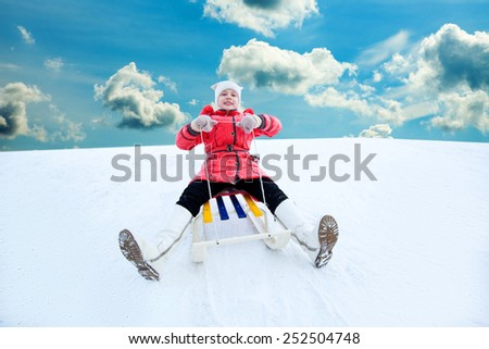 happy, cheerful, screaming child in red clothes rides the hills on sleds, beautiful clouds - stock photo