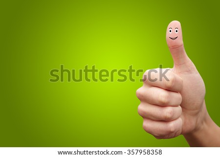 Happy cheerful smiley finger on green background. Ok - stock photo