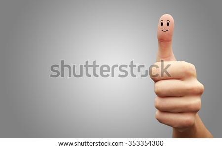Happy cheerful smiley finger on grey background. Ok - stock photo