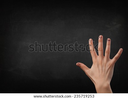 Happy cheerful smiley fingers looking at empty black chalboard
