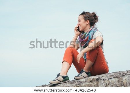 happy cheerful smiley woman sitting on a rock by the sea talking on phone with sunglasses on summer - stock photo