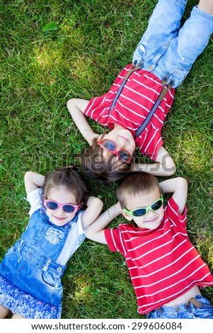 Happy cheerful smiling children, laying on a grass, wearing sunglasses, smiling at the camera, shot from above - stock photo