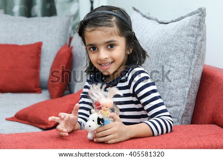 Happy cheerful smiling cute little girl child/ kid playing with her toys Kerala, India. 6 year old Indian daughter sitting on a couch holding her toys. Joyful young girl with naughty looks. people - stock photo