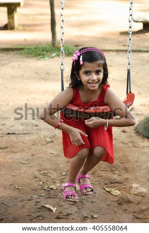 Happy cheerful smiling cute little girl/ child/ kid swinging in park, Kerala, India. Naughty playful young Indian daughter enjoying evening day out, summer vacation/ holiday, Playing school play area - stock photo