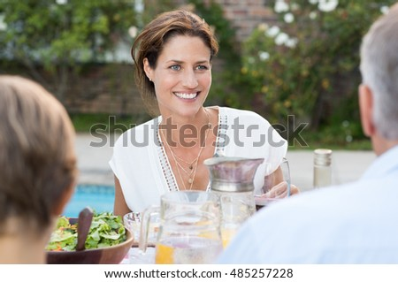 Happy cheerful woman sitting with family enjoying meal. Happy mature woman sitting at dining table outdoor with her family. Portrait of a happy young cheerful woman eating lunch with parent and child.