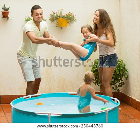 Happy cheerful young parents and little daughters having fun in pool outdoor  - stock photo