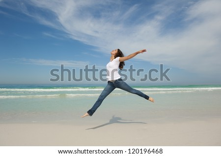 Happy cheerful young pretty woman jumping full of joy at beach with arms up, isolated with ocean and blue sky as background and copy space. - stock photo