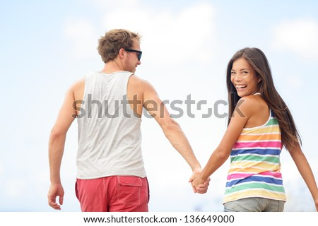 Happy cheerful young trendy couple holding hands walking together outside smiling having fun being in love. Beautiful young multiethnic couple, Asian woman, Caucasian man. - stock photo