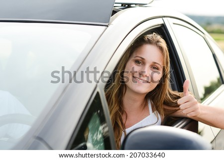 happy cheerful young woman driving her brand new car with new drivers license - stock photo