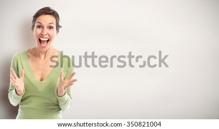 Happy cheerful young woman over gray background. - stock photo