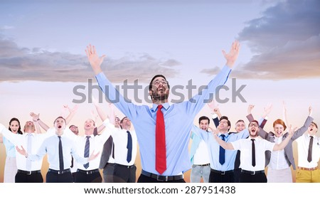 Happy cheering businessman raising his arms against beautiful orange and blue sky - stock photo