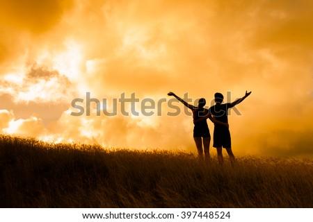 Happy cheering couple enjoying beautiful sunset. Happiness concept. - stock photo
