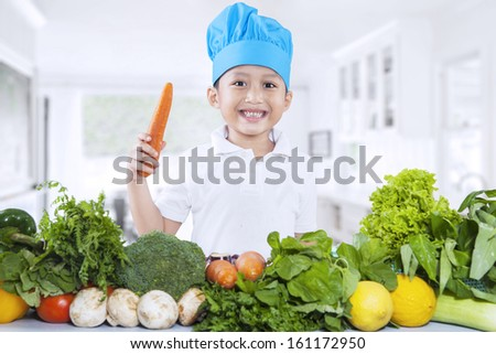 Happy chef boy holding a carrot with fresh vegetables at home - stock photo