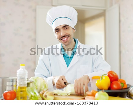 Happy chef cooking vegetarian lunch on cutting board  - stock photo