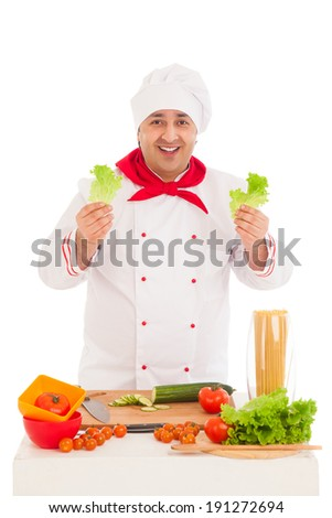 happy chef holding leaf of salad and cooking with fresh vegetables  wearing red and white uniform over white background  - stock photo