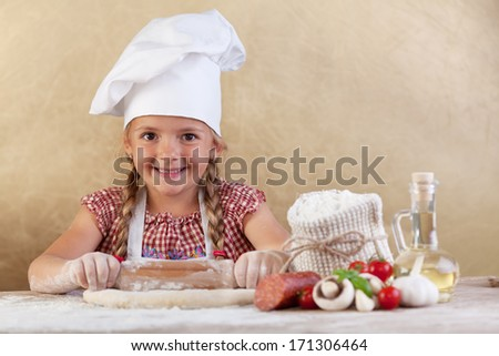 Happy chef little girl stretching the dough - with food ingredients on the side of table - stock photo