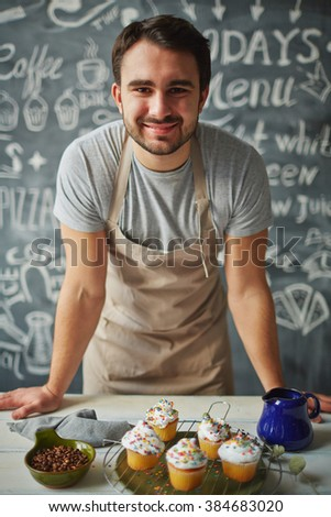 Happy chef looking at camera behind counter of desserts - stock photo