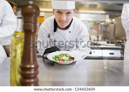 Happy chef presenting her salad in the kitchen - stock photo