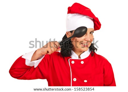 Happy chef woman holding big spoon in front of eye isolated on white background