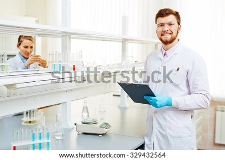 Happy chemist in white-coat, eyeglasses and gloves making notes in lab on background of his assistant - stock photo