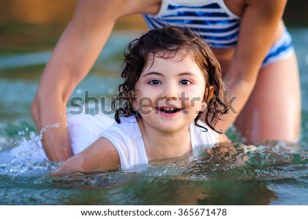 Happy child, a cute little girl swimming with her mom in the ocean on a hot summer day - stock photo