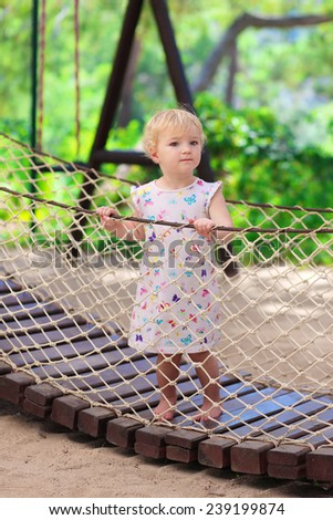 Happy child, adorable blonde toddler girl, having fun outdoors climbing in playground on a sunny summer day