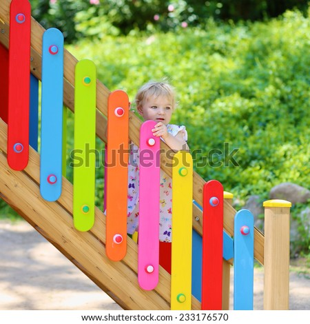 Happy child, adorable blonde toddler girl, having fun outdoors hiding in playhouse in playground on a sunny summer day - stock photo