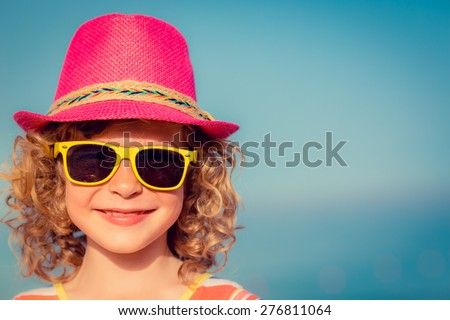 Happy child against sea and sky background. Summer vacation and travel concept - stock photo