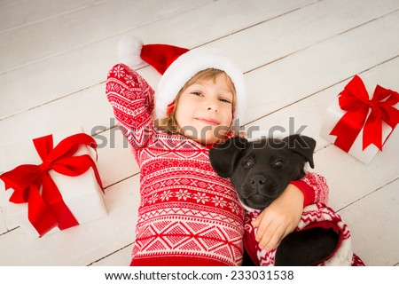 Happy child and dog with Christmas gift. Kid dressed in Santa Claus hat. Baby having fun at home. Xmas holiday concept - stock photo