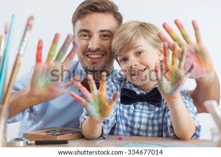 Happy child and father with colorful hands - stock photo