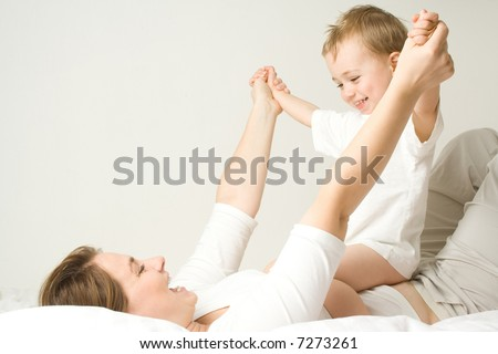 Happy child and mother wearing white attire in white bed and room.