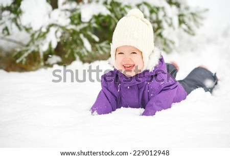 Happy child baby girl in snow outdoors in winter - stock photo