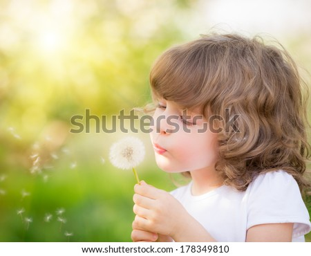 Happy child blowing dandelion outdoors in spring park - stock photo